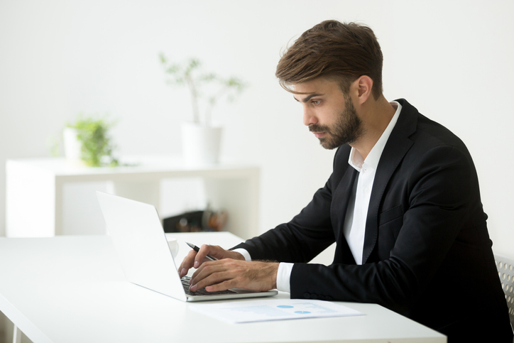 Serious businessman typing emails to business partners